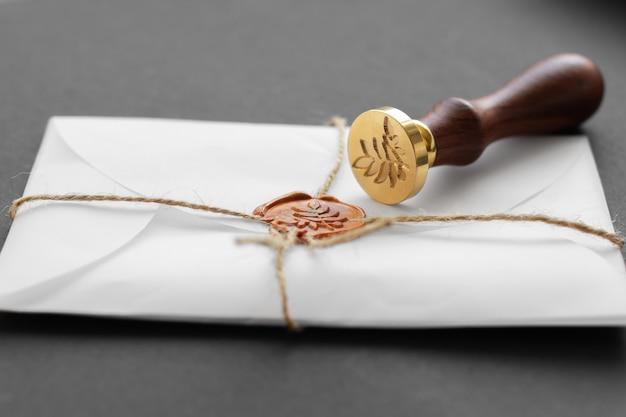 Notar wachsstempel. weißer umschlag mit braunem wachssiegel, goldener stempel. responsive design-modell, flach gelegt. stillleben mit postzubehör.