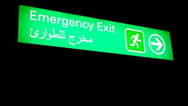 Notausgangsschild an einem internationalen flughafen im nahen osten mit arabischen informationen