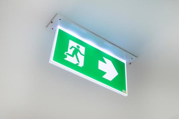Notausgangstür ausgangstür an der decke. grünes fluchtwegzeichen, das den weg zeigt.