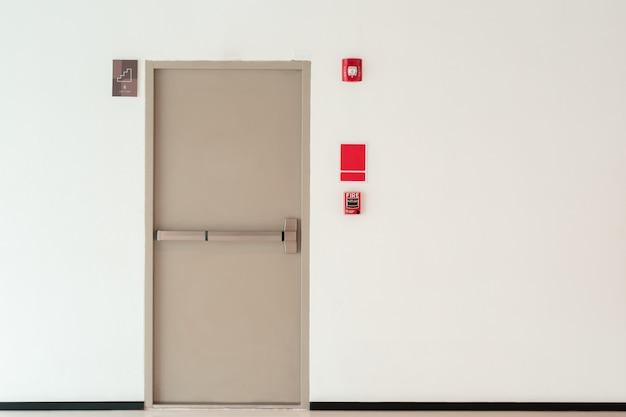 Notausgangtürhintergrund mit kopienraumwand, innenbürogebäude