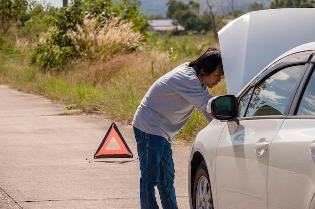 Notauszeichen und fahrer nahe defektem auto auf straße.