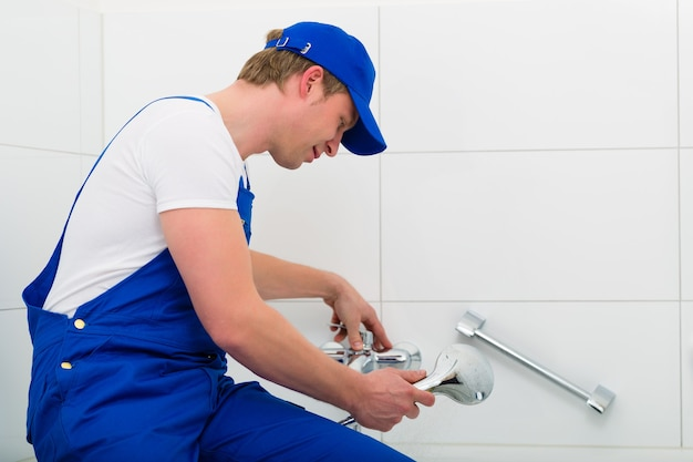 Notdienst - klempner oder auftragnehmer, der eine nicht funktionierende dusche in der badewanne repariert