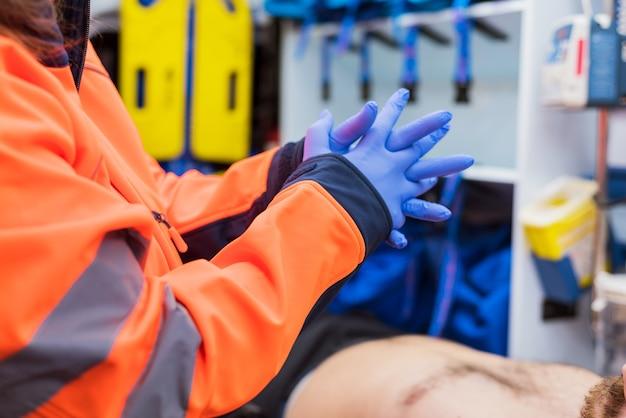 Notdoktor, der auf handschuhe im krankenwagen sich setzt