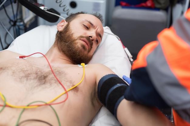 Notdoktor, der blutdruck eines patienten im krankenwagen überprüft