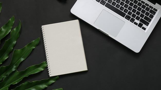 Notebook-blatt-laptop mit draufsicht auf dunklem hintergrund