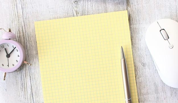 Notebook, das auf einem hölzernen arbeitstisch neben einem laptop liegt