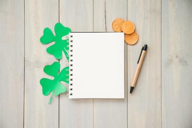 Notebook in der nähe von münzen und dekorativen klee
