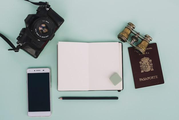 Notebook in der nähe von reisebedarf und technologien