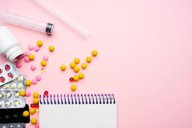 Notebook medizin medikamente pharmazeutische schmerzmittel rosa hintergrund