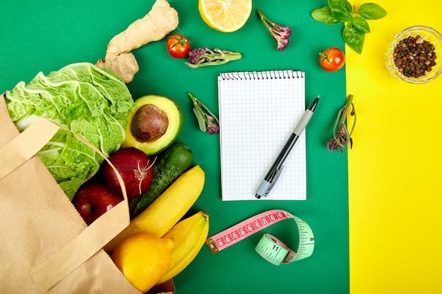 Notebook mit papiertüte voller früchte
