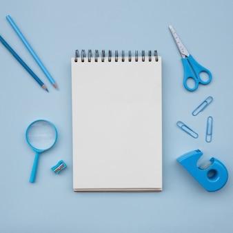 Notebook mit schere lupe bleistiftspitzer auf hellblauen hintergrund