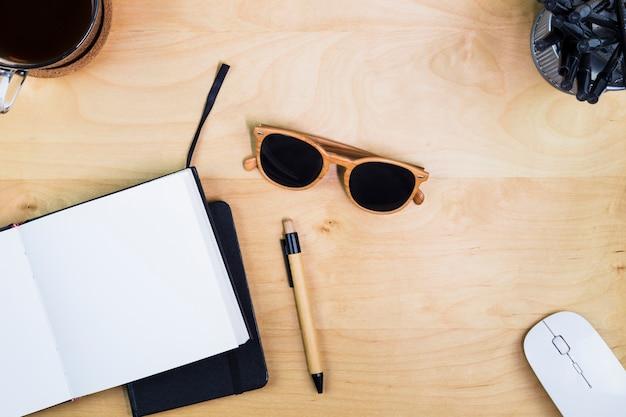 Notebook mit sonnenbrille auf dem tisch