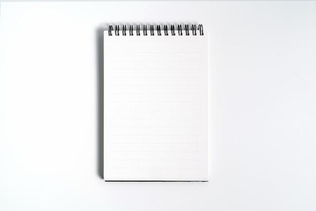 Notebook-modell mit sauberem schwarzem leerzeichen für design und werbung. notizblock mit verchromter feder und freier kopienraumschablone. auf dem grauen hintergrund.