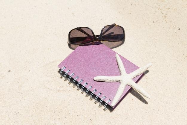 Notebook sonnenbrille und seestern am strand liegen