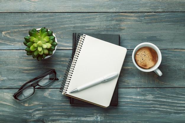 Notebook und tasse starken kaffee auf holzhintergrund.