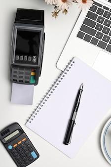 Notebook, zahlungsterminal, laptop-computer und taschenrechner auf weißem schreibtisch.