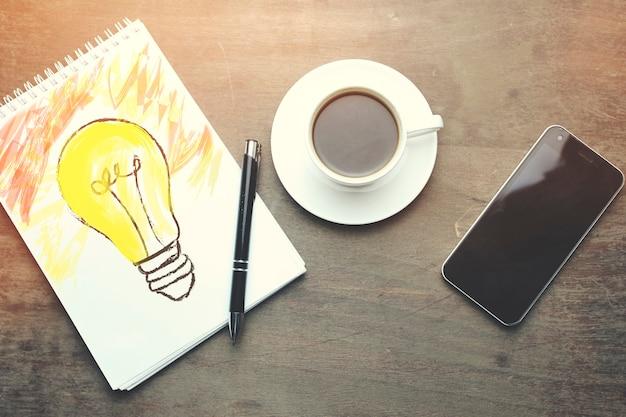 Notebookbirne, stift, telefon und kaffee auf holztisch
