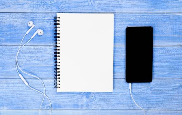 Notebooks, telefone und kopfhörer sind auf dem blauen schreibtisch platziert. mit kopienraum