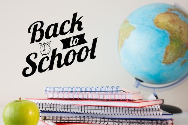 Notebooks und globus mit dem satz zurück in die schule