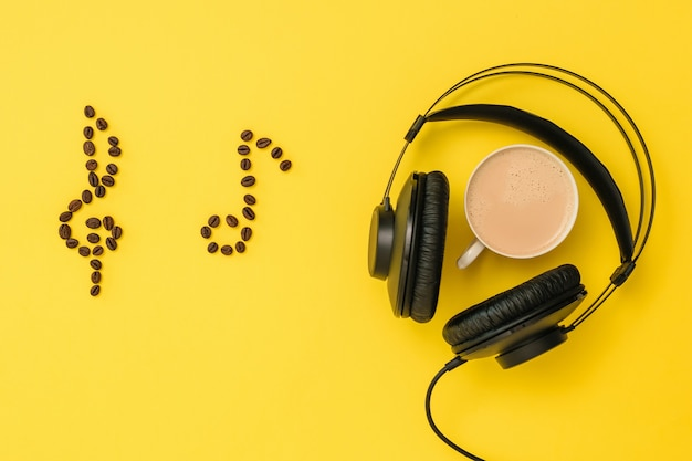 Noten von kaffeebohnen, kopfhörern und einer tasse kaffee auf gelbem grund. das konzept des musikschreibens. ausrüstung zum aufnehmen von musiktiteln. der blick von oben. flach liegen.