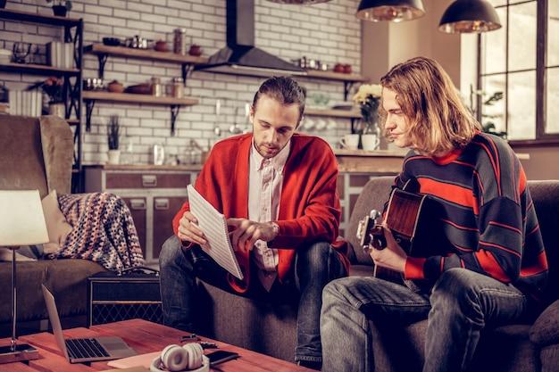 Notenbuch. erfahrener angenehmer gitarrenlehrer, der ein notenbuch hält, während er den schüler unterrichtet