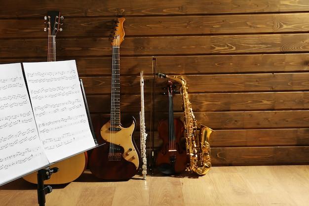 Notenhalter gegen musikinstrumente auf holzoberfläche