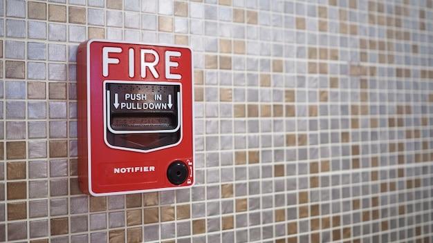 Notfall-feueralarm oder alarm- oder klingelwarnausrüstung in roter farbe im gebäude zur sicherheit.