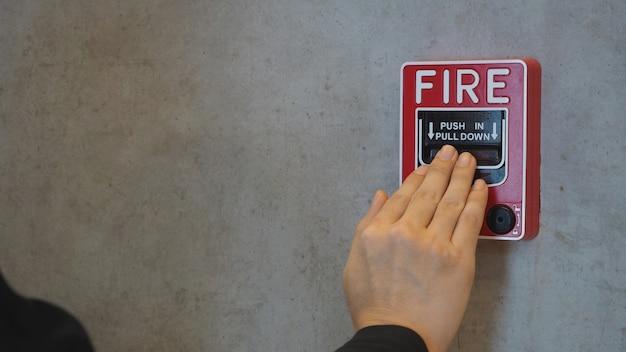 Notfall von feueralarm oder alarm oder klingelwarngerät und hand. im gebäude für die sicherheit.