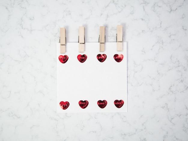 Notieren sie papier mit hölzerner wäscheklammer und herzformobjekten auf marmorhintergrund, glücklichem valentinstag, muttertag, flache lage, draufsicht
