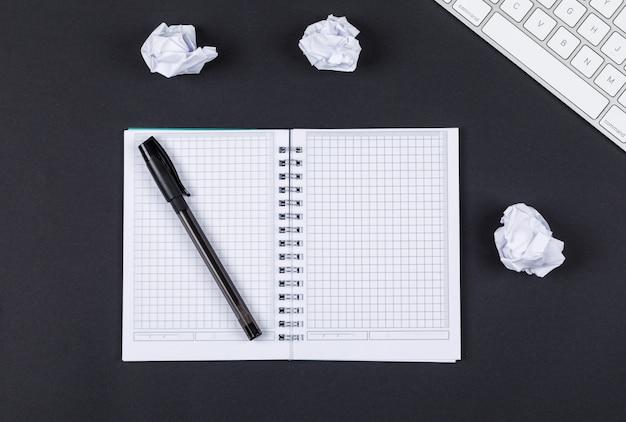 Notizaufnahmekonzept mit notizbuch, stift, zerquetschtem papier, tastatur auf schwarzer hintergrundoberansicht. horizontales bild