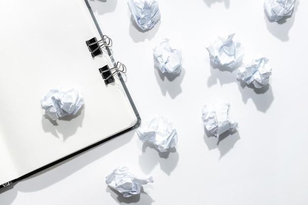 Notizblock auf einem weißen hintergrund mit zerstreuten zerknitterten anmerkungen