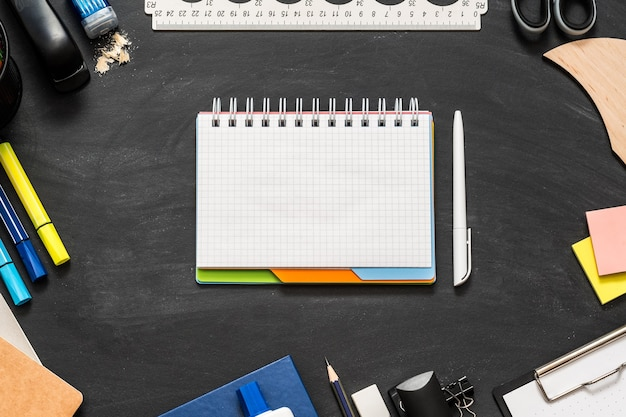Notizblock auf schultafel mit büromaterial