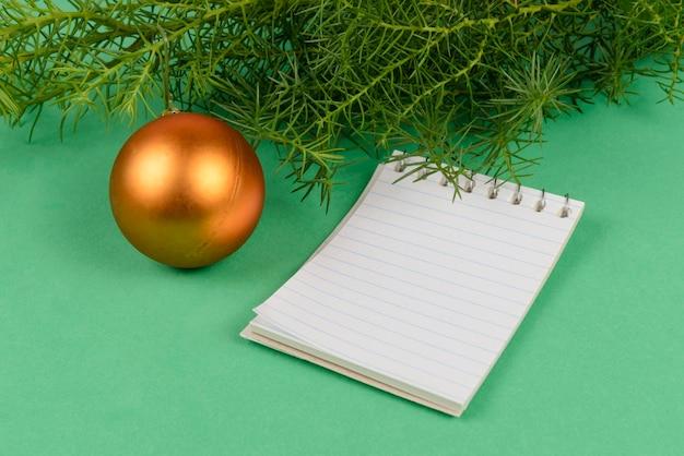 Notizblock aus papier neben zypressenzweigen auf grün.