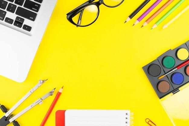 Notizblock, buntstifte, trennwand, schwarze brille, bunte clips, farben zum zeichnen und laptop