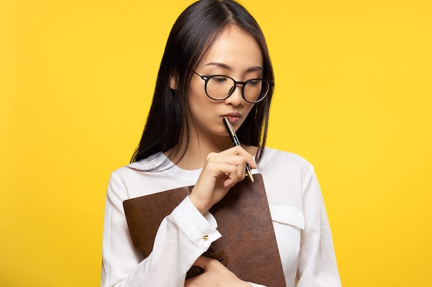 Notizblock des asiatischen aussehens der frau in den händen arbeiten gelben hintergrund