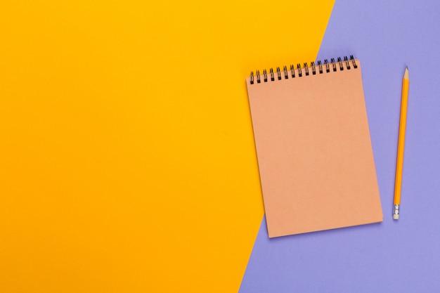 Notizblock des leeren papiers auf hellem zweifarbigem hintergrund für ihr design, draufsicht