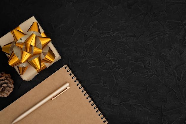 Notizblock, ein stift, ein geschenk und ein tannenzapfen auf schwarzem betonhintergrund