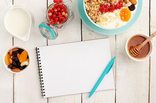 Notizblock für gewichtsverlustplan, gesundes frühstück der müslischale auf weißem holz