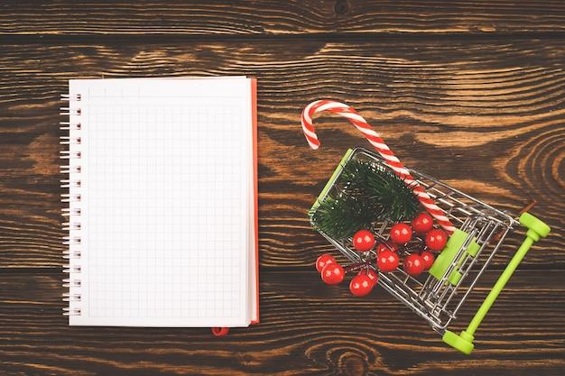 Notizblock für notizen im weihnachtsstil auf einem hölzernen hintergrund. einträge für silvester-shopping. ansicht von oben, flacher stil.