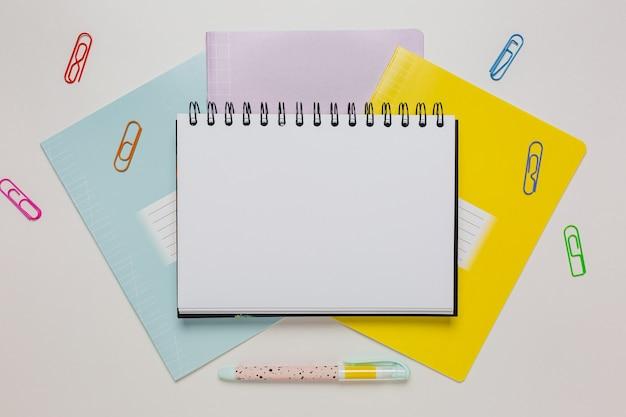Notizblock, heft und stift auf dem schreibtisch. mock-up im kopierraumbüro auf weißem hintergrund. zurück zur schule