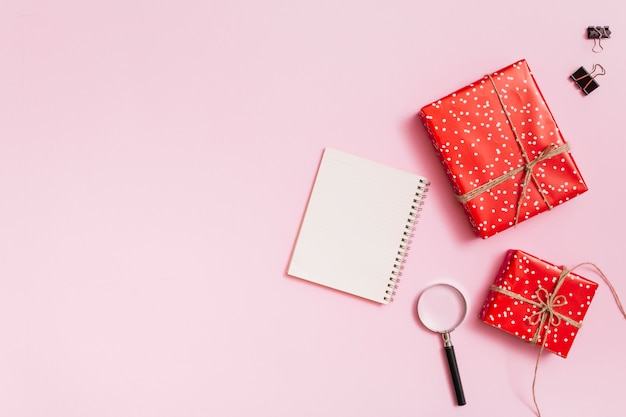 Notizblock in der nähe von geschenkboxen, clips und lupe