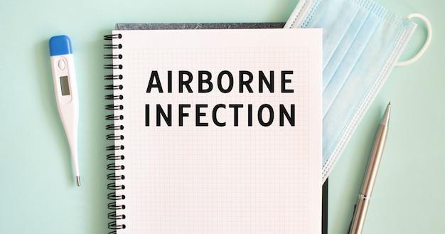 Notizblock, medizinische maske, thermometer und stift auf blau. airborne infection text in einem notizbuch