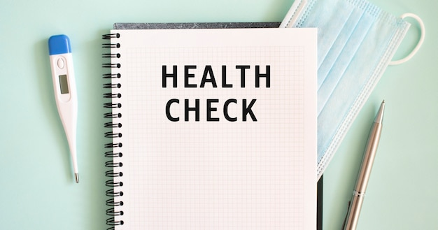 Notizblock, medizinische maske, thermometer und stift auf blauem hintergrund. gesundheitsprüfung text in einem notizbuch. medizinisches konzept.