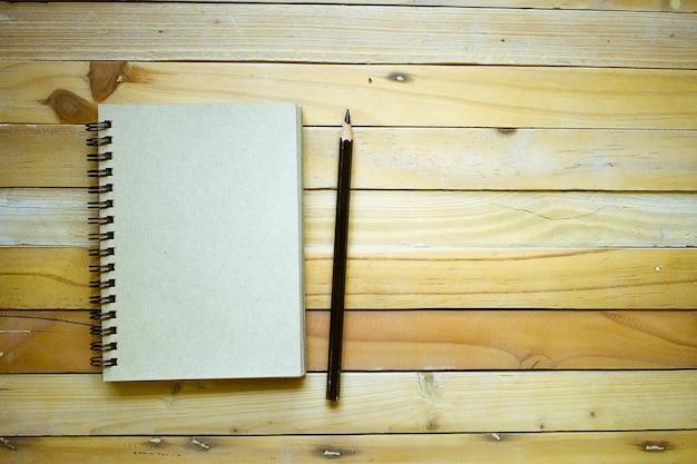 Notizblock mit bleistift auf hölzernem bretthintergrund unter verwendung der tapete für bildung