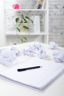 Notizblock mit einem stift und zerknitterten papieren