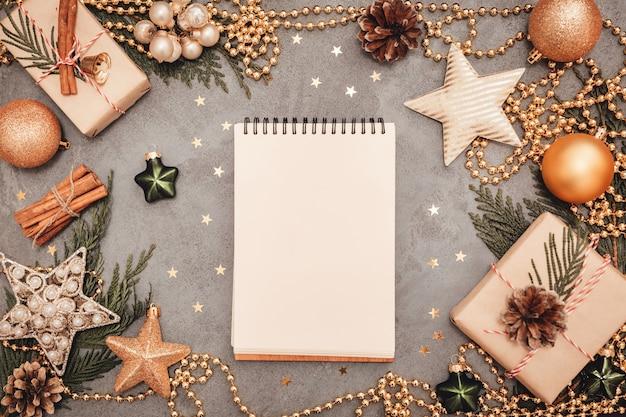 Notizblock mit feiertagsdekorationen auf grauem betonhintergrund, copyspace. flatlay-konzept für weihnachten und neujahr.