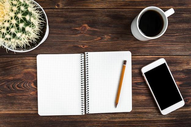 Notizblock mit gelbem stift und kaffee auf hölzernem hintergrund. ziele für das neue jahr. planungs- und zeitplankonzept. aufgabenliste.