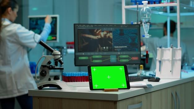 Notizblock mit grünem bildschirm, der im labor mit mock-up-monitor und chroma-key-anzeige arbeitet, während ein professioneller ingenieur die virusentwicklung im hintergrund testet. hightech-entwicklungslabor.