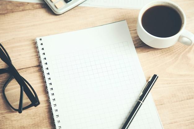 Notizblock mit kaffee und taschenrechner