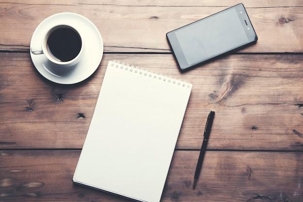 Notizblock mit kaffee und telefon auf dem tisch